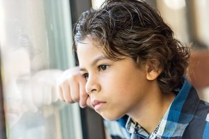 Pensive hispanic little boy looking through a window