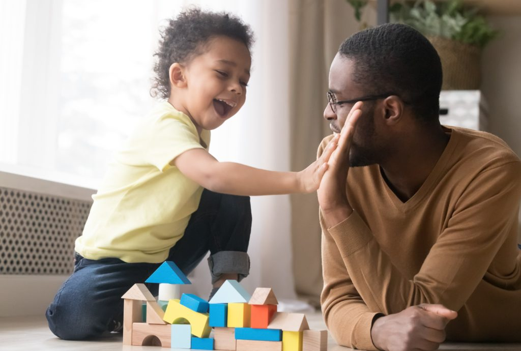 African American father with toddler son playing with wooden constructor